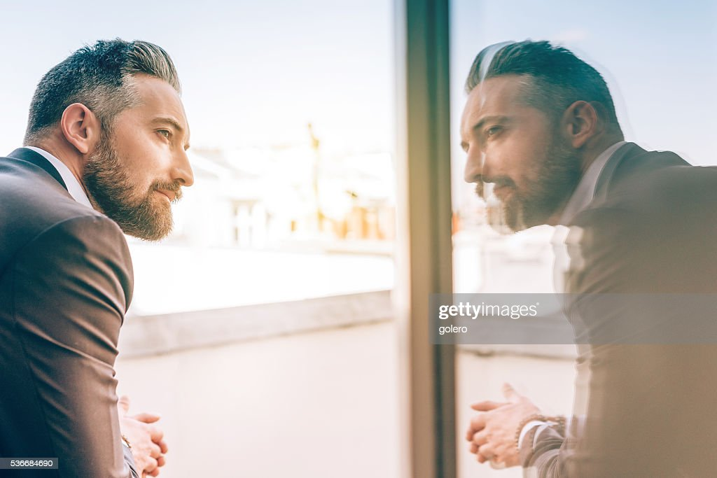 bearded business man reflecting himself in window glass : Stock Photo