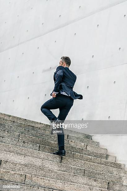 bearded business man running up outdoor stairway