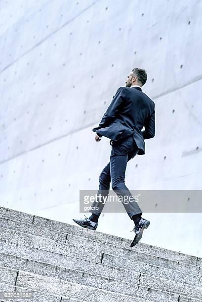 bearded business man running up stone stairway