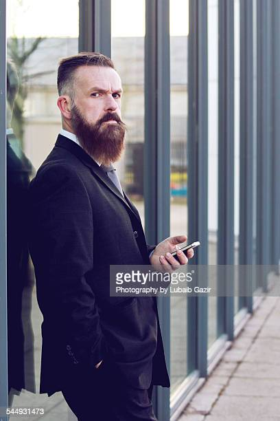 bearded businessman holding his phone - gillingham stock pictures, royalty-free photos & images