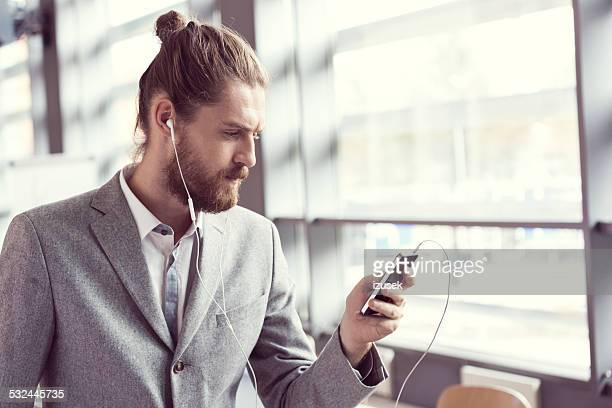 Bearded businessman listening to music using phone