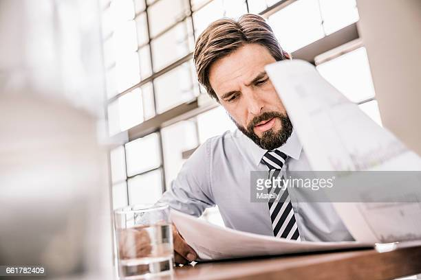 bearded businessman looking down at paperwork - bureaucracy stock pictures, royalty-free photos & images