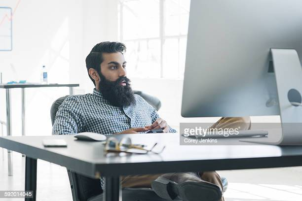 Bearded businessman sitting in front of computer