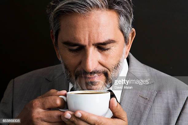 Bearded businessman smelling coffee