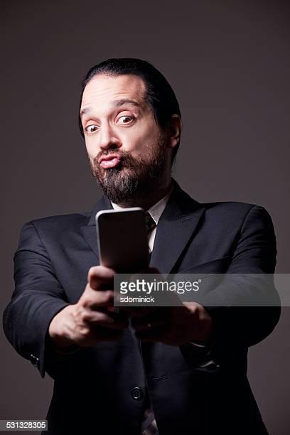 さしセルフィーをかぶり笑うヒゲのあるビジネスマンを承っております。