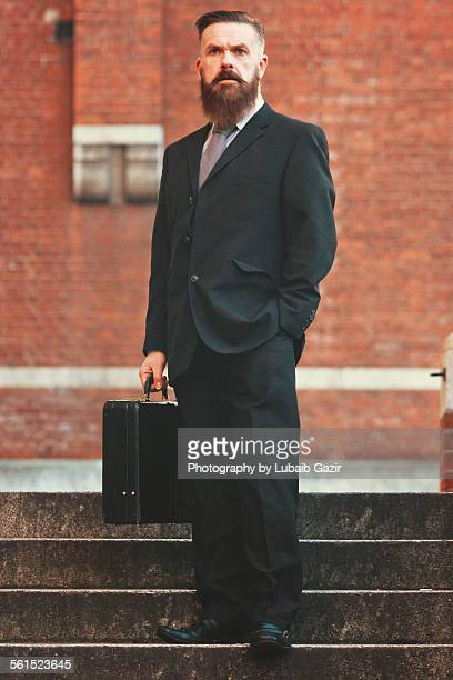 Bearded businessman walking down with briefcase