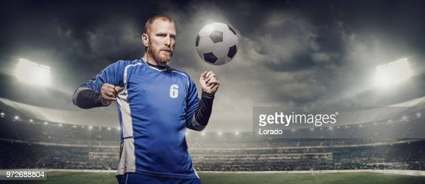 bearded caucasian football player controlling a soccer ball in front of stadium lights - international soccer event stock pictures, royalty-free photos & images