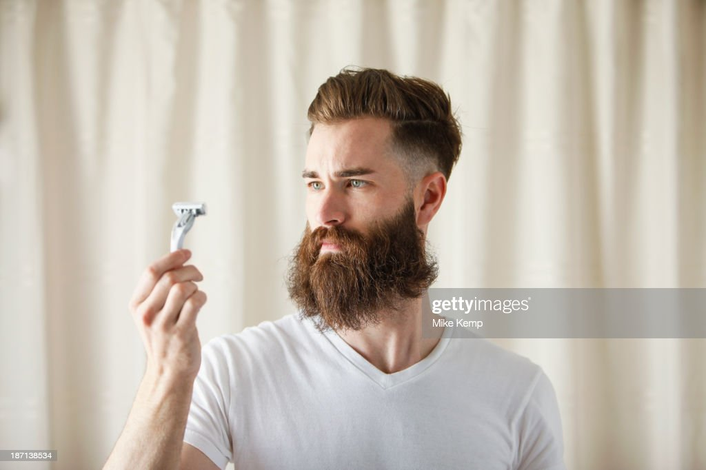 Bearded Caucasian man examining razor : Stock Photo