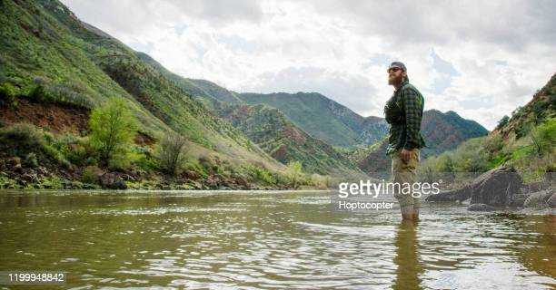 a bearded caucasian man in his twenties with a backwards baseball cap and a pfd (personal floatation device) wades into the colorado river in western colorado under an overcast sky - khaki trousers stock pictures, royalty-free photos & images