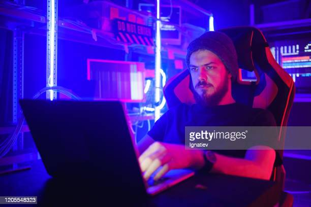 bearded computer hacker coding on laptop on a background of monitors in neon lights. - surfing the net stock pictures, royalty-free photos & images