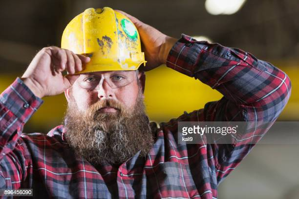 Bearded construction worker putting on hardhat