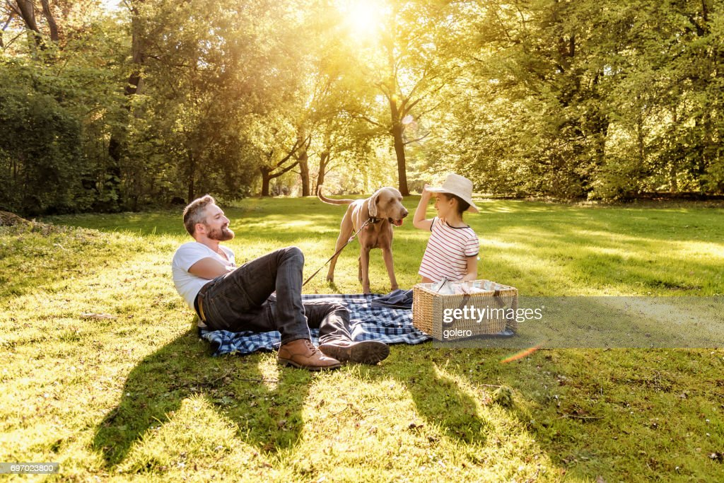 bearded father and teenage daughter at picnic with dog in park : Stock Photo