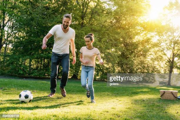bearded father and teenage daughter playing soccer on meadow