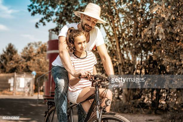 bearded father and teenage daughter together on bicycle outdoors