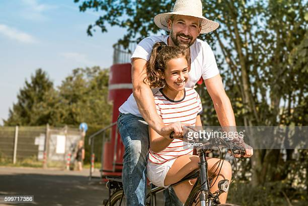bearded father and teenage daughter together on one bicycle