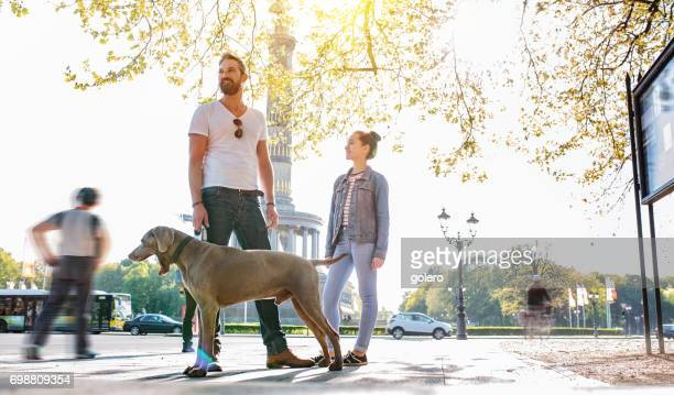 bearded father and teenage daughter with weimaraner dog at victory column - central berlin stock photos and pictures