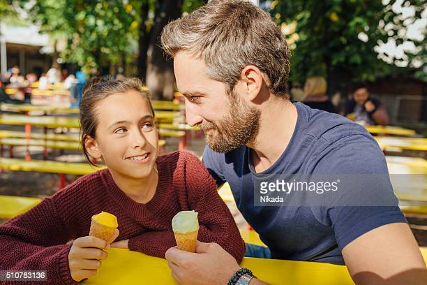 bearded father eating ice cream with daughter
