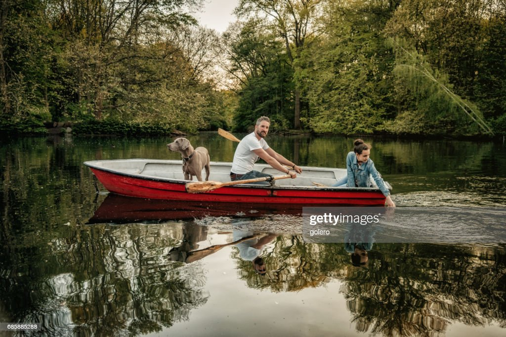 bearded father sculling row boat with teenage daughter and dog : Stock Photo