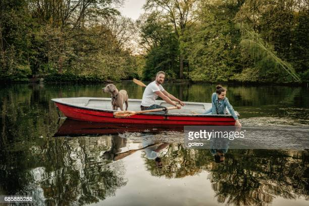 bearded father sculling row boat with teenage daughter and dog
