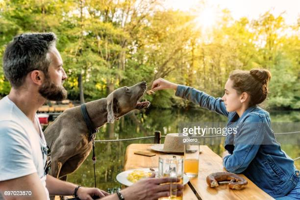 bearded father with teenage daughter and dog eating in beer garden