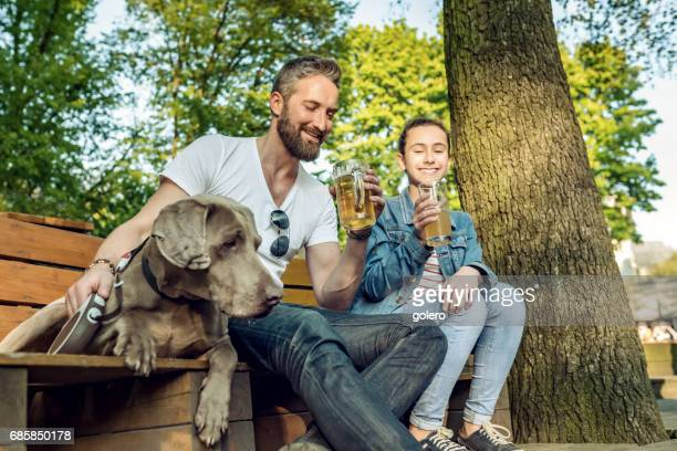 bearded father with teenage daughter and dog relaxing in beer garden