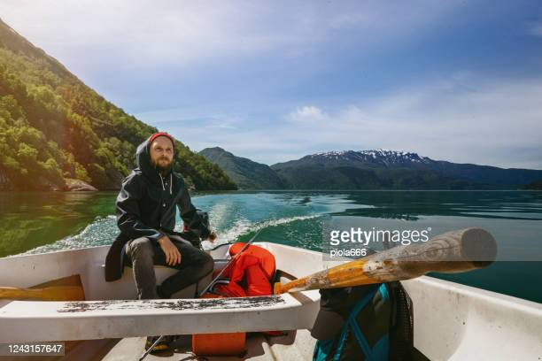 bearded fisherman on a small fishing boat: sailing in a fjord in norway - vintage raincoat stock pictures, royalty-free photos & images
