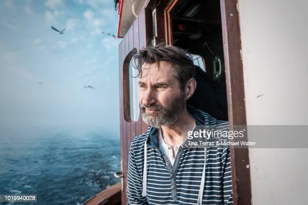 bearded fisherman on his ship. - fischer stock-fotos und bilder