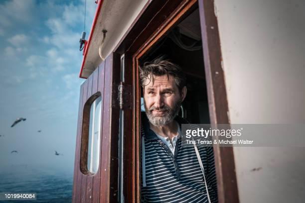 bearded fisherman on his ship. - schleswig holstein stock-fotos und bilder