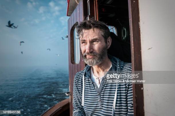 Bearded fisherman on his ship.