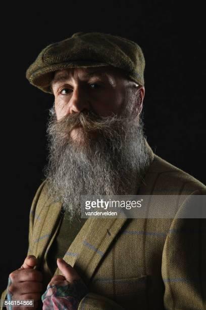 入れ墨の手で彼の 50 代の髭の紳士 - ツイード ストックフォトと画像