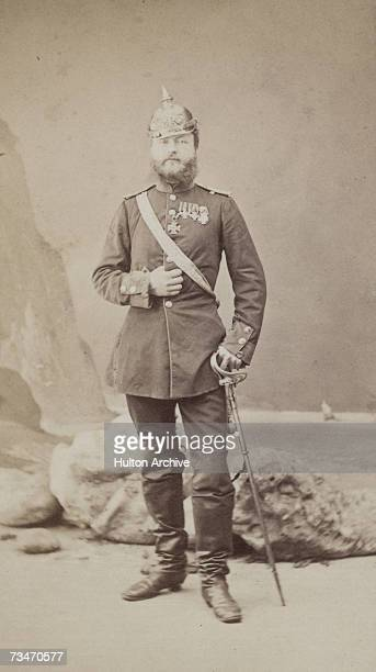 A bearded German soldier in full uniform with his sword 1860s