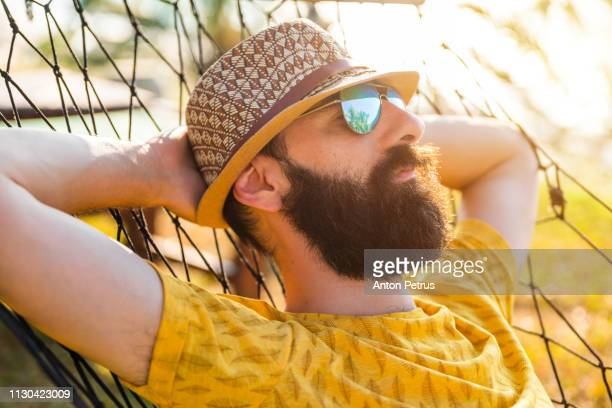 Bearded guy resting in a hammock by the ocean