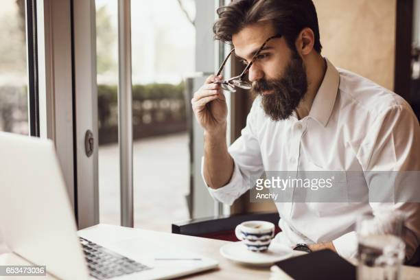 Bearded guy taking off his glasses after finishing his work