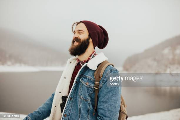 bearded hiker wearing warm clothes and binoculars around his neck - one man only stock pictures, royalty-free photos & images