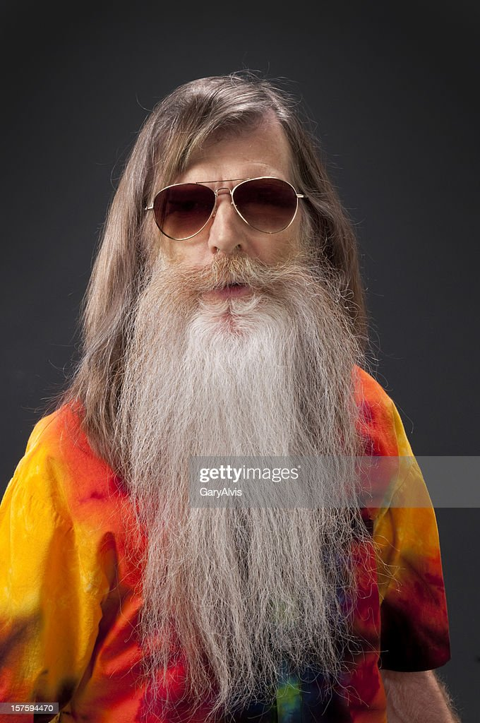 bearded hippie man w/sunglasses and tie-dye shirt/isolated : Stock Photo