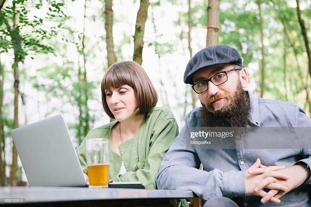 Slip a vita bassa e un Biergarten ragazza di lavoro sul computer portatile : Foto stock