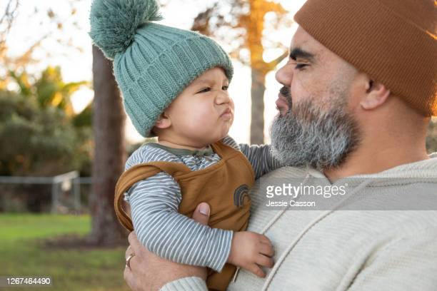 bearded hipster dad and baby pulling funny face - pacific islanders stock pictures, royalty-free photos & images