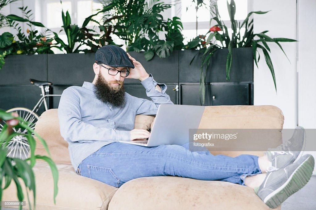 hipster lay su un divano e il lavoro al computer portatile : Foto stock