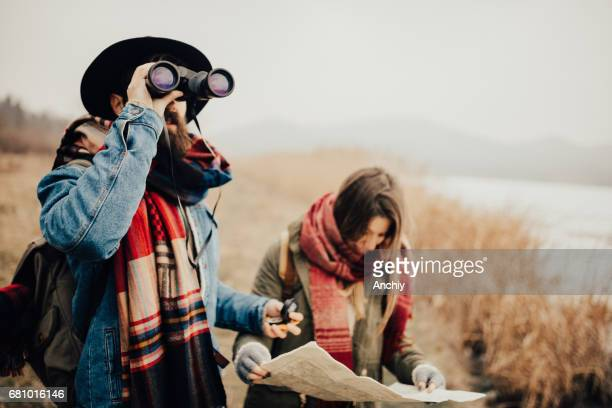 Bearded hipster looking through binoculars while his friend is checking the map for directions