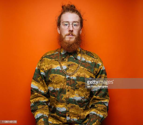 bearded hipster on orange background - gold chain stock pictures, royalty-free photos & images