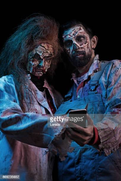Bearded Male and Redhead Female Zombie couple using a smartphone