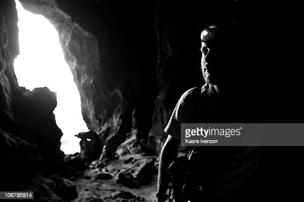 Bearded male explores a limestone cave with his headlamp.