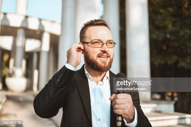 bearded male journalist explaining latest news and going live from city center - presidential candidate stock pictures, royalty-free photos & images