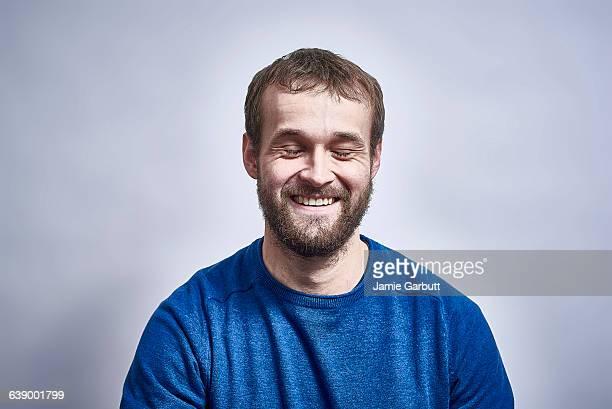 bearded male smiling with his eyes closed - augen geschlossen stock-fotos und bilder