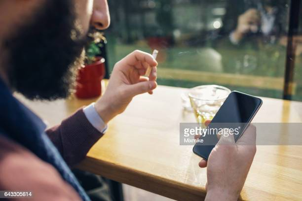 Bearded male smoking and drinking alcohol