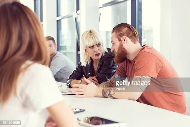 bearded man and blonde woman working on laptop - izusek stock pictures, royalty-free photos & images