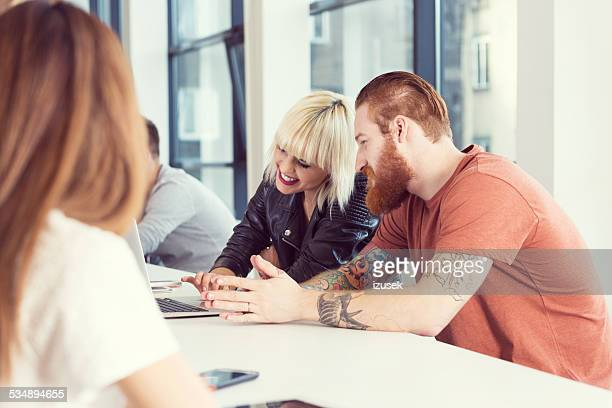 bearded man and blonde young woman working on laptop - izusek stock pictures, royalty-free photos & images