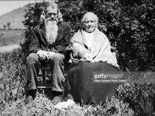 Bearded man and wife sitting outdoors 1910s