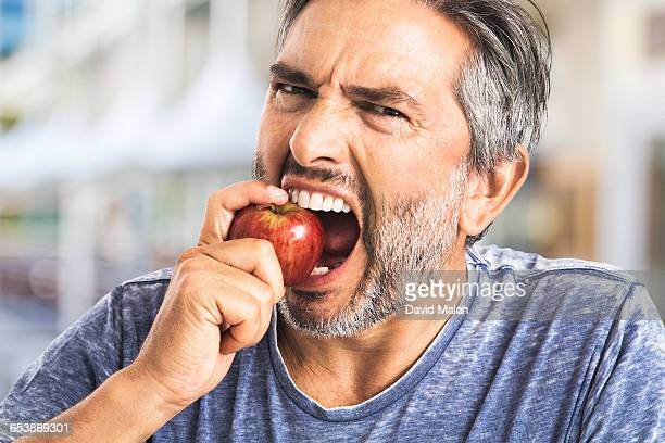 Bearded man biting an apple