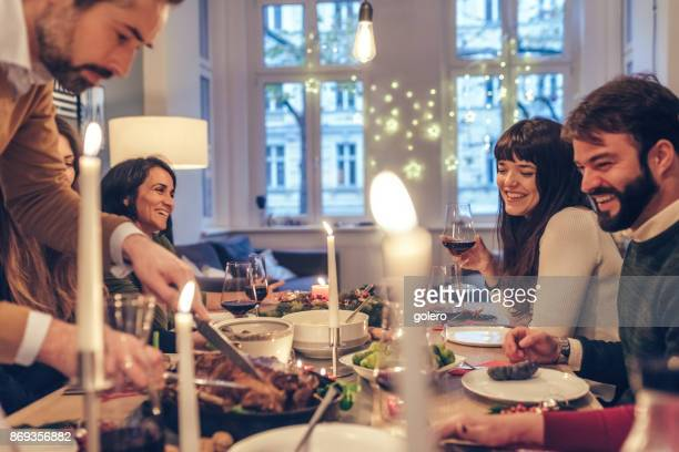 bearded man carving celebrity roast at christmas table